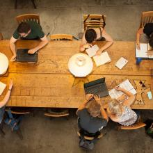 A birds-eye view of students studying individually at a long desk or work table.
