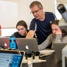 A professor consults with students working on laptops in a lab.