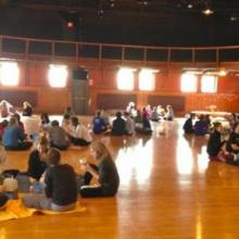 Students seated in groups inside a sunlit dance studio